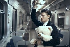 Young man is riding in an empty subway car. In his hands is a teddy bear Royalty Free Stock Photo