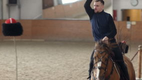 Young man riding his horse and swinging his sword. A Cossack horseman cuts through a Cossack hat. stock footage
