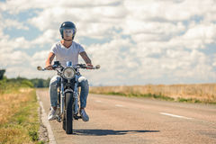 Young man riding his motorbike on open road Stock Photos