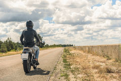 Young man riding his motorbike on open road Royalty Free Stock Images