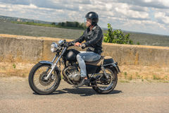 Young man riding his motorbike on open road Stock Images