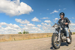Young man riding his motorbike on open road Royalty Free Stock Image
