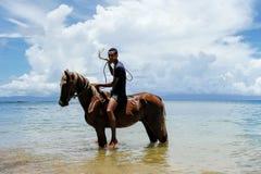 Young man riding horse on the beach on Taveuni Island, Fiji Stock Photos