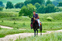 A young man riding horse on the meadow Royalty Free Stock Photos