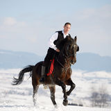 Young man riding horse outdoor in winter Stock Photography