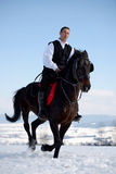 Young man riding horse outdoor in winter Royalty Free Stock Photos