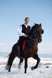 Young man riding horse outdoor in winter Royalty Free Stock Photo