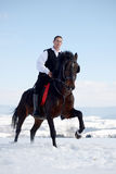 Young man riding horse outdoor in winter Stock Photos