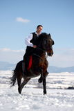Young man riding horse outdoor in winter Stock Image