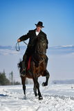 Young man riding horse outdoor in winter Royalty Free Stock Image