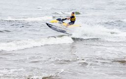 Young man riding on jet ski on the waves. Sventoji, Lithuania - August 13, 2018: Young man riding on jet ski performing tricks on the sea waves at summer in royalty free stock image