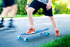 Young man riding on a longboard. Longboard on the road in sunny weather. People around skateboard. Stock Photo