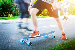 Young man riding on a longboard. Longboard on the road in sunny weather. People around skateboard. Stock Image