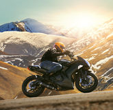 Young man riding motorcycle on asphalt country road with sun shi. Ning and mountain background use for sport activities,male leisure and journey theme stock photo