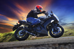 Young man riding motorcycle on curve of asphalt country road. Against dusky sky use for sport activities,male leisure and journey theme stock image