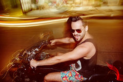 Young man riding a motorcycle in night without helmet. Long exposure portrait of hispanic yong man wearing sunglasses riding a motorcycle in night without helmet stock images