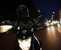 Young Man riding a motorcycle at night through the streets of Beijing stock image