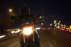 Young Man riding a motorcycle at night through the streets of Beijing Stock Photography