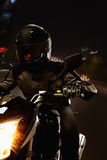 Young Man riding a motorcycle at night through the streets of Beijing Royalty Free Stock Image