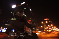 Young Man riding a motorcycle at night through the streets of Beijing Royalty Free Stock Photos