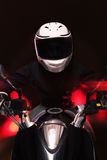 Young man riding a motorcycle at night through the streets of Beijing, front view Royalty Free Stock Image