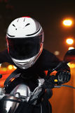 Young man riding a motorcycle at night through the streets of Beijing, front view Royalty Free Stock Photos