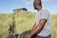 Young Man Riding Mountain Bike By Dunes Stock Photography