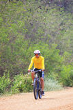 Young man riding mountain bike in dusty road use for sport leisu Stock Photos