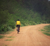 Young man riding mountain bike in dusty road use for sport leisu Royalty Free Stock Image