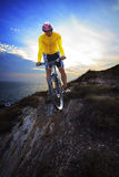Young man riding moutain bike mtb on land dune against dusky sky royalty free stock photos