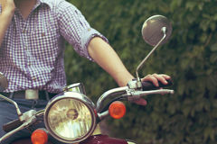 Young man riding old retro scooter Royalty Free Stock Images