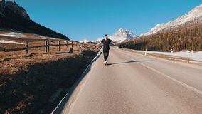 Young man riding on the road and keeps balance in a small skateboard on the backdrop of the forest and mountains. Mid shot stock video footage