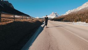 Young man riding on the road and keeps balance in a small skateboard in the middle of the Alps. Mid shot stock footage