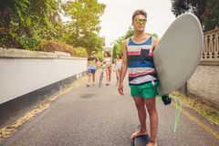 Young man riding on skate and holding surfboard Stock Photo