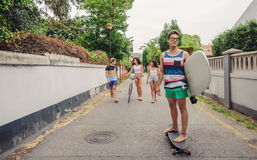 Young man riding on skate and holding surfboard Stock Photos