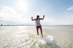Young man riding on skimboard on summer beach Stock Photos