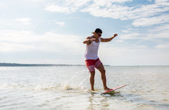 Young man riding on skimboard on summer beach Royalty Free Stock Photos