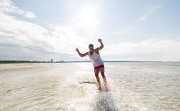 Young man riding on skimboard on summer beach Royalty Free Stock Image