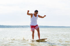 Young man riding on skimboard on summer beach Royalty Free Stock Images