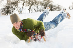 Young Man Riding On Sledge In Snowy Landscape Stock Photography