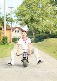 Young man riding small motorbike Stock Photo