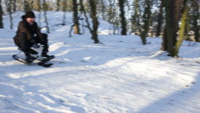 Young man riding a snow scooter stock footage
