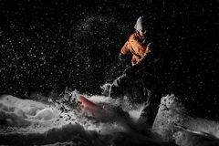 Young man riding on the snowboard in the mountain resort in the night stock photography