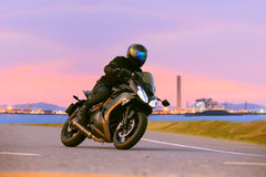 Young man riding sport touring motorcycle on asphalt highways ag. Ainst beautiful lighting of urban industry scene use as modern people lifestyle and holiday Royalty Free Stock Image