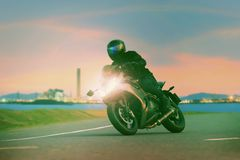 Young man riding sport touring motorcycle on asphalt highways ag. Ainst beautiful lighting of urban industry scene use as modern people lifestyle and holiday stock photography