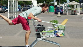 A young man is riding a trolley in a parking lot near a supermarket. The basket is full of products. Fun and good mood stock video