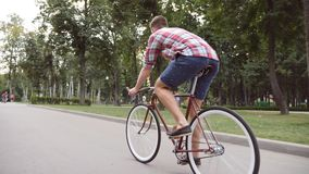 Young man riding vintage bicycle at the park alley. Sporty guy cycling outdoor. Healthy active lifestyle. Rear Back view. Close up Slow motion royalty free stock images