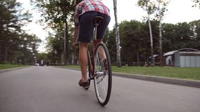 Young man riding a vintage bicycle at the park road. Sporty guy cycling outdoor. Healthy active lifestyle. Low angle of Stock Images