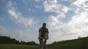 Young man riding vintage bicycle at the rural road over field. Sporty guy cycling along country trail outdoor. Male stock video footage