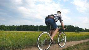 Young man riding vintage bicycle at the rural road over field. Sporty guy cycling along country trail outdoor. Male. Cyclist riding bike in the countryside stock video